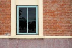 Hellblaues Fenster auf Backsteinmauer Stockbild