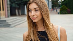 Hellbraune behaarte junge Frau des Gesichtes, die Kamera steadicam Schuss betrachtet Porträtschönheit auf städtischer Stadtstraße stock video