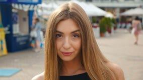 Hellbraune behaarte junge Frau des Gesichtes, die oben Kameraabschluß betrachtet Porträtschönheit auf städtischem Stadtstraßenhin stock video footage