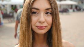 Hellbraune behaarte junge Frau des Gesichtes, die oben Kameraabschluß betrachtet Porträtschönheit auf städtischem Stadtstraßenhin stock footage