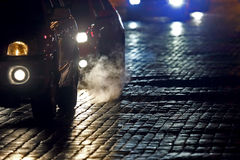 Helle Autos gehen nachts auf der Pflasterung Lizenzfreies Stockfoto