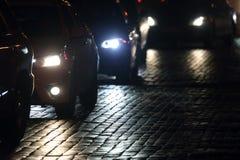 Helle Autos gehen nachts auf der Pflasterung Lizenzfreies Stockbild