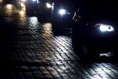 Helle Autos gehen nachts auf der Pflasterung Stockbilder