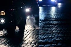 Helle Autos gehen nachts auf der Pflasterung Lizenzfreie Stockfotos