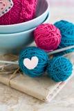 Helle Bälle des Garns in den blauen Platten und des Herzens gemacht vom Filz Stockfotografie