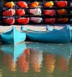 Helle blaue Kanus vor roten Kajaks Stockfotos