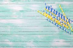 Helle blaue und gelbe Papierstrohe auf Türkis hölzernem backgrou Stockfotografie