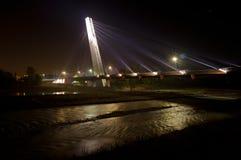 Helle Brücke über dunklem Fluss Stockfotografie