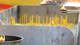 Helle duftende Stäbe der Leute von Kerzen des guten Glücks und des Wachses über Feuer Buddhistische Religion stock video footage