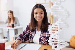 Helle Energiefrau, die eine Forschungsarbeit auf Genetik schreibt lizenzfreies stockbild
