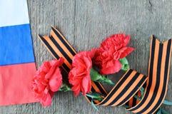Helle Feiertagskarte am 23. Februar Rote Gartennelken und russische Flagge auf rustikalem hölzernem Hintergrund Vaterland-Verteid stockbilder