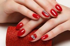 Helle festliche rote Maniküre stockfoto