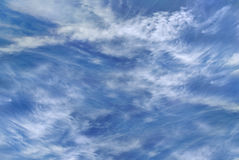 Helle flaumige Wolken gegen einen klaren blauen Himmel Lizenzfreie Stockbilder
