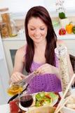 Helle Frau, die zu Hause einen Salat mit Schmieröl isst Lizenzfreie Stockfotos