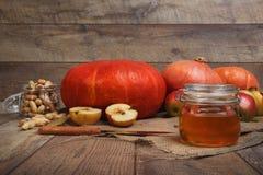 Helle frische Kürbise, geschnittene Äpfel, Erdnüsse und ein Glasgefäß voll Honig auf einem hölzernen Hintergrund Autumn Harvest Lizenzfreies Stockbild