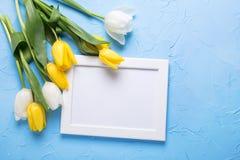 Helle gelbe Tulpenblumen und leerer Rahmen auf dem Blau gemasert Lizenzfreies Stockfoto