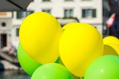 Helle gelbe und grüne Ballone auf einer Stadtstraße Lizenzfreies Stockfoto