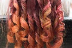 Helle gelockte Verschlüsse des langen Haares mit Funkeln von Hochrot zu Rot stockfotos