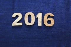 Helle hölzerne Darstellungsnummer 2016 auf dem Hintergrund der Jeans Lizenzfreie Stockfotografie