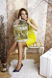 Helle junge hübsche Frau, die mit einem Käfig aufwirft Stockfoto