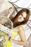 Helle junge hübsche Frau, die mit einem Käfig aufwirft Stockbild