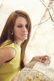 Helle junge hübsche Frau, die mit einem Käfig aufwirft Lizenzfreies Stockfoto
