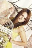 Helle junge hübsche Frau, die mit einem Käfig aufwirft Lizenzfreie Stockfotos