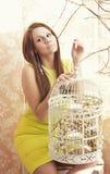 Helle junge hübsche Frau, die mit einem Käfig aufwirft Stockfotos