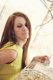 Helle junge hübsche Frau, die mit einem Käfig aufwirft Lizenzfreies Stockbild