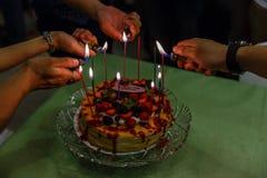 Helle Kerzen auf dem Krepp backen die auf die Oberseite mit Mischbeeren und Erdbeersoße zusammen Lizenzfreies Stockbild