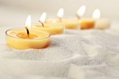 Helle Kerzen des Tees im Sand Stockbilder