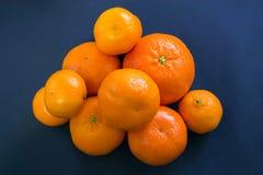 Helle Mandarinen liegen harmonisch auf einem dunkelblauen Hintergrund stockfotografie