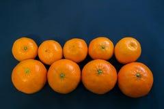 Helle Mandarinen liegen harmonisch auf einem dunkelblauen Hintergrund stockfotos