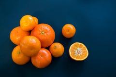 Helle Mandarinen liegen harmonisch auf einem dunkelblauen Hintergrund lizenzfreie stockfotos