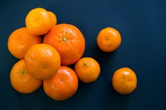 Helle Mandarinen liegen harmonisch auf einem dunkelblauen Hintergrund stockbild