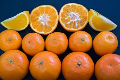 Helle Mandarinen liegen harmonisch auf einem dunkelblauen Hintergrund Scheiben der Zitrusfrucht und der Schale lizenzfreie stockbilder
