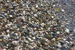 Helle mehrfarbige Kiesel auf Strand im Mittelmeer stockfotos