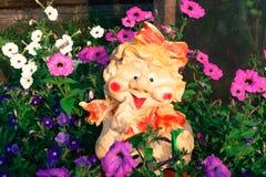 Helle mehrfarbige Petunien und nette Gartenskulptur im Zustand lizenzfreie stockbilder