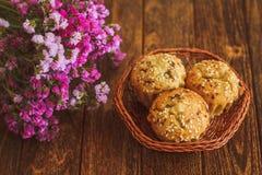 Helle Muffins mit indischem Sesam auf dunklem hölzernem Hintergrund Lizenzfreie Stockfotos