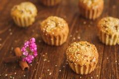 Helle Muffins mit indischem Sesam auf dunklem hölzernem Hintergrund Stockbilder