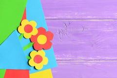 Helle Papierblumen, farbiges Papier bedeckt auf hölzernem Hintergrund mit leerem Raum der Kopie für Text Lustige Blumenkarte Stockbild
