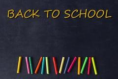 Helle Pastellzeichenstifte liegen in Folge auf einer schwarzen Schulbehörde Chil Stockfotos