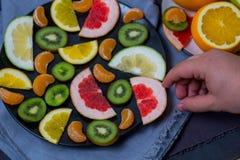 Helle reife köstliche Fruchtzitrusfruchtorangen schnitten in ein großes Schwarzblech auf einer Blaugewebehintergrundgeschirrtuchm lizenzfreies stockbild