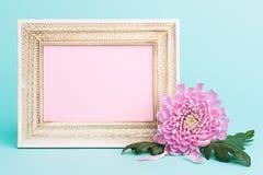Helle rosa Blume auf einer Tabelle mit leerer Bilderrahmen-Grußkarte Glückliches Mutter ` s Tag-, Frauen ` s Tag-, Valentinsgruß  Stockfotos