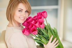 Helle rosa Blumen in den Händen des Mädchens. Lizenzfreie Stockbilder