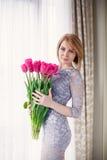 Helle rosa Blumen in den Händen des Mädchens. Lizenzfreies Stockbild