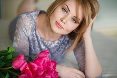 Helle rosa Blumen in den Händen des Mädchens. Lizenzfreie Stockfotografie