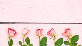Helle Rosen auf rosa hölzernem Hintergrund Lizenzfreies Stockfoto