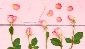 Helle Rosen auf rosa hölzernem Hintergrund Stockfotografie