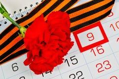 Helle rote Gartennelke eingewickelt mit George-Band, das auf dem Kalender mit gestaltetem am 9. Mai Datum - Victory Day-Grußkarte Lizenzfreie Stockfotos